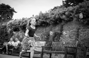young girl chasing bubbles in documentary photoshot in the gardens of Non Such Park Surrey