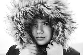 Black & White lifestyle fashion portrait of a woman in Surrey pulling in her big fur hood with her hands