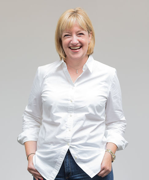 Full length body shot of buisness woman in white blouse laughing in casual pose for company headshots