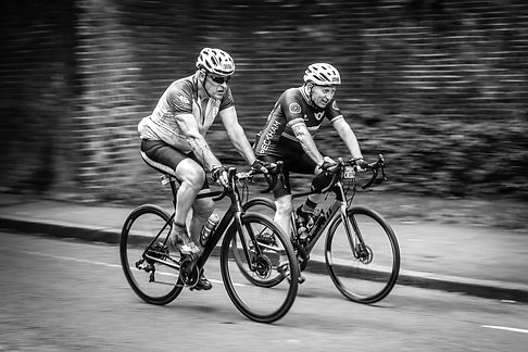 Black and white lifestyle photo of two male cyclists dressed in lycra racing in a road cycle race in South West London