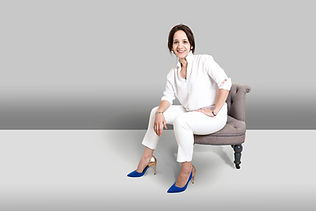 Woman dressed in white with blue shoes sits for business portrait personal branding shoot in Surrey