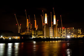 Battersea power station at night with river thames in foreground
