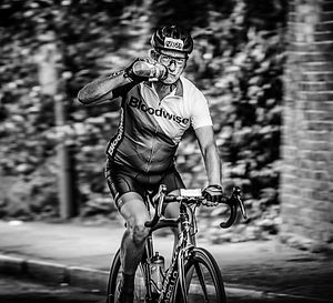 Black and white photo of a Man taking a drink during a cycle event race in South London