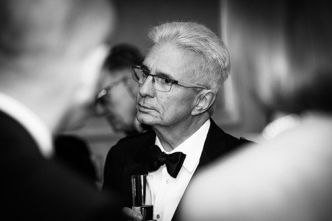 Guest at a black tie birthday event in Surrey listening to another guest captured unobtrusively the photographer