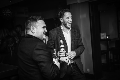 Two men enjoying a drink at an event in Surrey