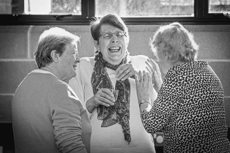 documentary photographer caputures three woman chatting and laughing at an event in Surrey