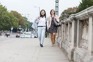 two business woman walking across Hampton Court bridge smiling for personal branding photography shoot in West London