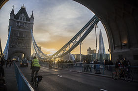 London Commuters early evening going on Tower Bridge with sun setting behind the Shard
