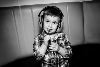 little boy with headphones on at sips a drink at event