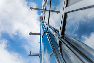 architectural photography of outside of Moden building looking up to clouds and blue sky