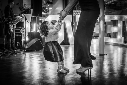 Documentry style event photography at a wedding reception of a little girl dancing with her mum
