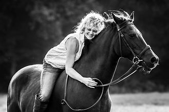 Black and white documentary lifestyle portrait photoshoot of a woman on horse back showing her horse some love in Surrey