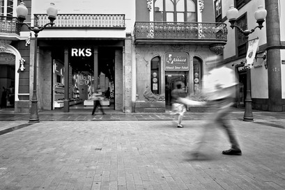 spanish high street with shoppers walking passed using slow shutter speed