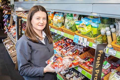 Retail promotional photoshoot of store worker filling shelves with grocery products in Surrey