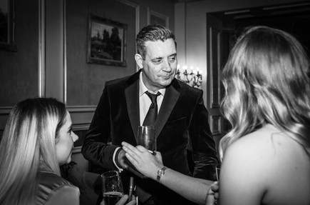 Party guest in a black dinner jacket chatting to women at birthday event