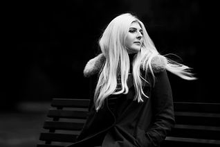 Black & White documentary portrait of a blonde girl sitting on a park bench in Ewell Surrey with her hair blowing in the wind