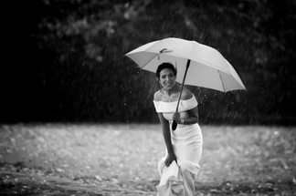 Black and white photo of a bride with an umbrella sheilds from the pouring rain in Surrey
