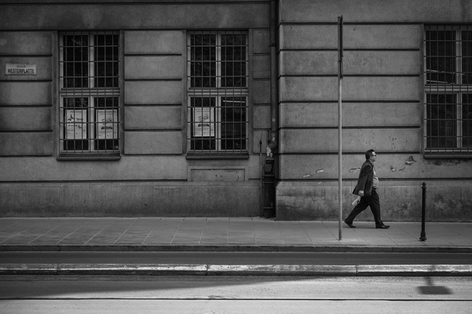 black and white photo of man walking down the street