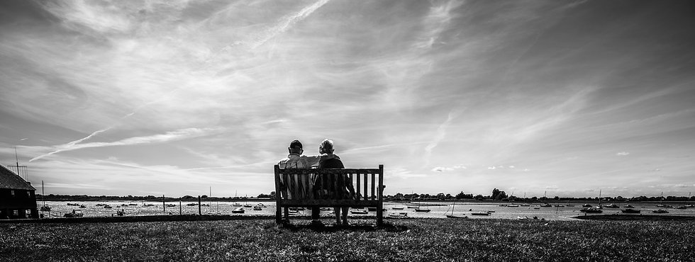 Black & White lifestyle portrait of an old couple sitting on a bench having a cuddle looking over Bosham Harbour in Sussex