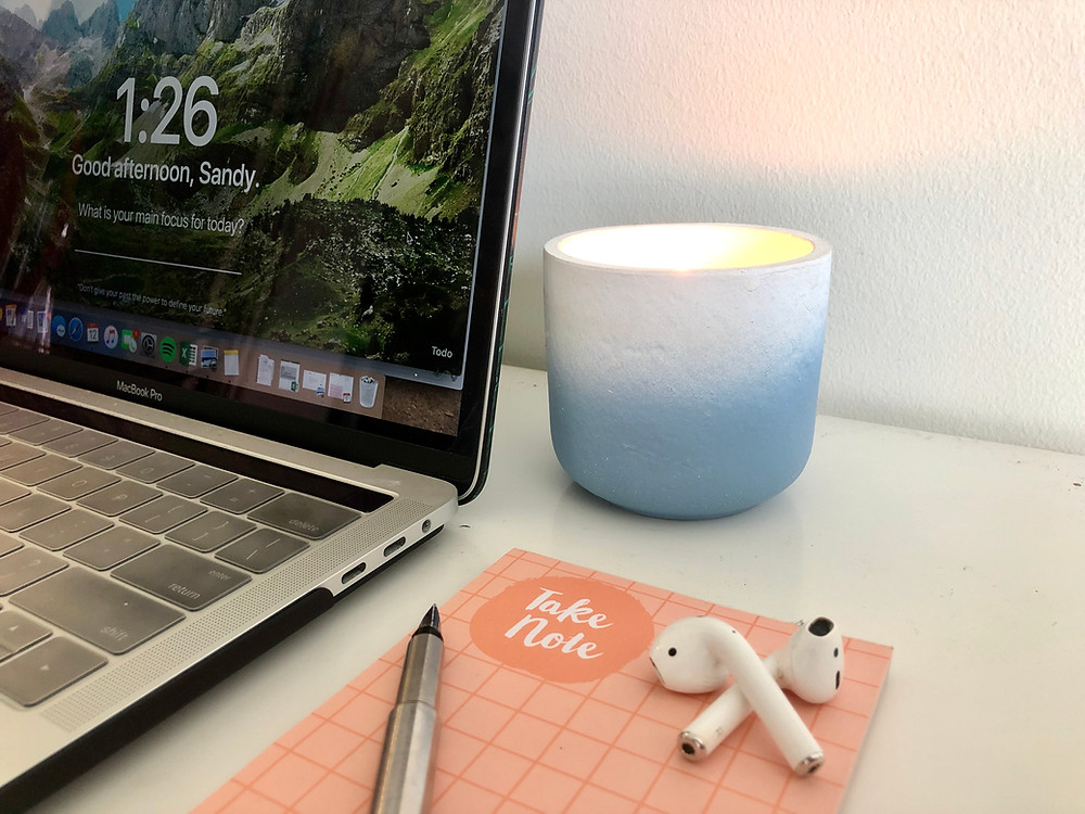Macbook Pro besides a note pad, fountain pen, airpods, and a lit candle