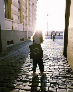 Girl in the sun on a cobble street starting off day with a morning walk or stroll