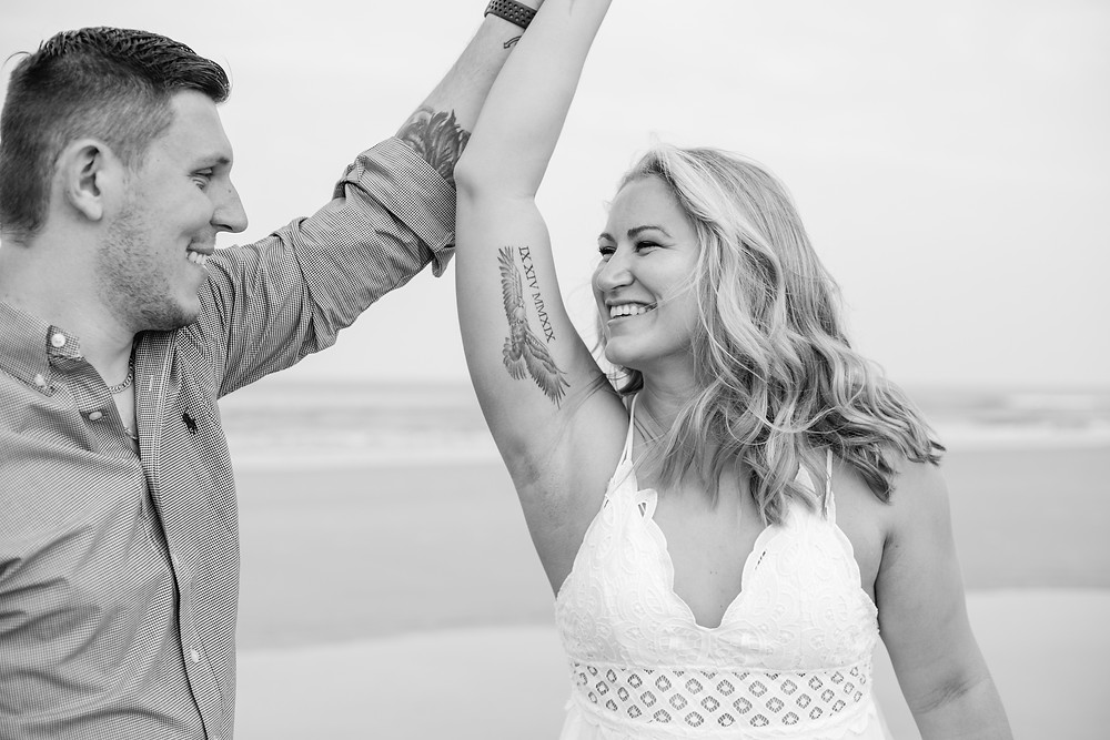 black and white happiness engagement session light and airy beach vibes on cresent beach in butler beach with bride and groom florida photographer st. augustine florida photographer wedding diamond ring