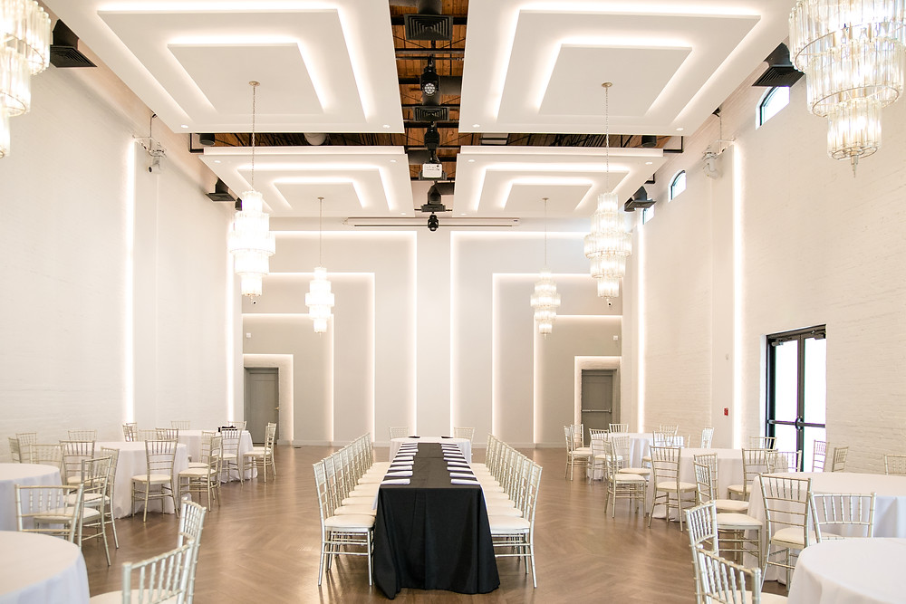 gorgeous white geometric lines in the ballroom and main floor of the clay theatre in green cove springs vaulted ceilings with gorgeous chandeliers