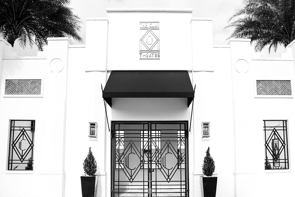 lovely black and white entrance to the clay theatre in green cove springs with gorgeous awning and lovely wrought iron accents with the letter c on them with palm trees