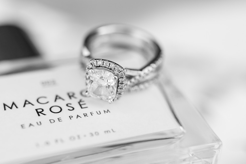 detail photosgraph of engagement ring and wedding band beautiful details at kelly farms styled photo shoot in st. augustine florida diamond ring perfume ribbon wedding venue
