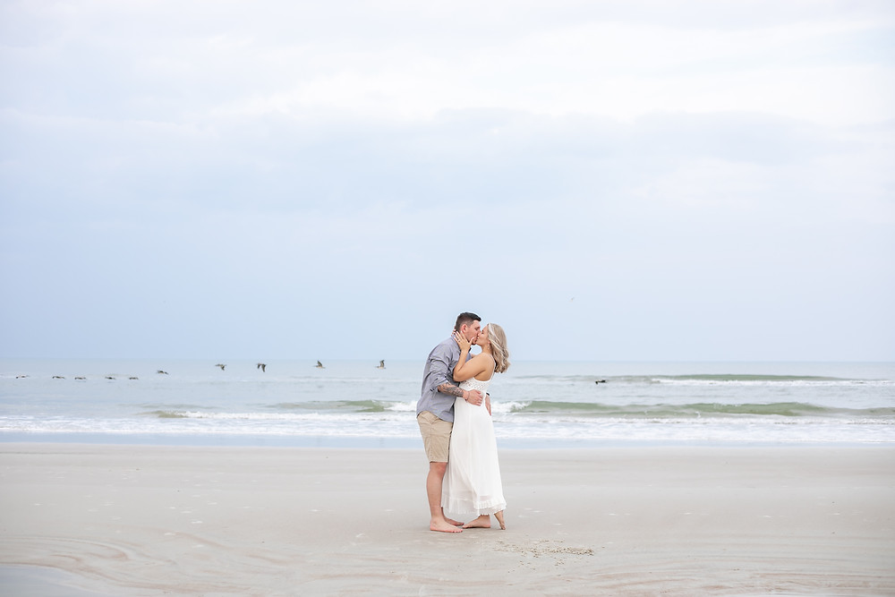 sunset engagement session on butler beach crescent beach st. augustine beach in florida adorable couple white and bright and light airy whimsical birds flying ocean front wedding