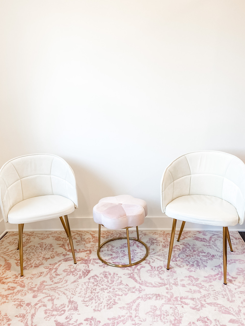sitting area in tebault bridal boutique with white chairs and a lovely pink persian rug and side table