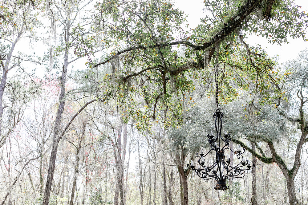 beautiful chandelier at tuckers farmhouse with large oak trees and rustic features for bride and groom and shabby chic decor at tuckers farmhouse in green cove springs florida with all the lovely details for any bride and groom country decor