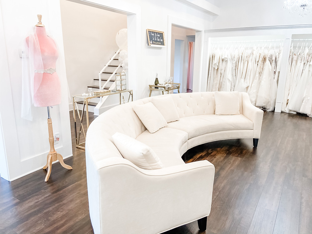 large beige, white couch placed directly across a three way mirror in a bridal shop with gowns, glitter and sparkle