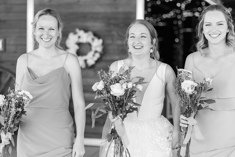 fun laughter bridesmaids bride bouquets gorgeous black and white barn wedding vibe light and airy wedding venue in st. augustine florida jacksonville florida photograrpher