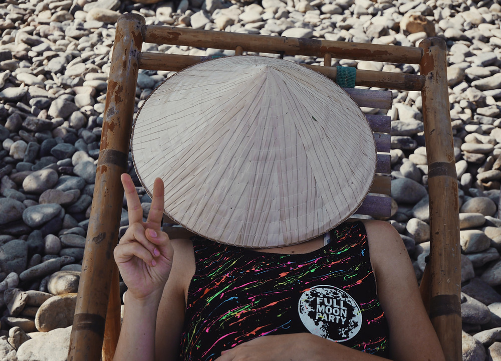 Girl laying on beach chair with Vietnamese hat