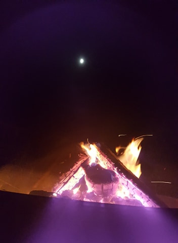 Christopher Lake June 5, 2020  I took this photo on a beautiful summer evening while i spent time with my family having a hotdog roast. While we sat by the fire we noticed a ring around the moon. I tried to capture the moon in the background of the fire because it was beautiful.