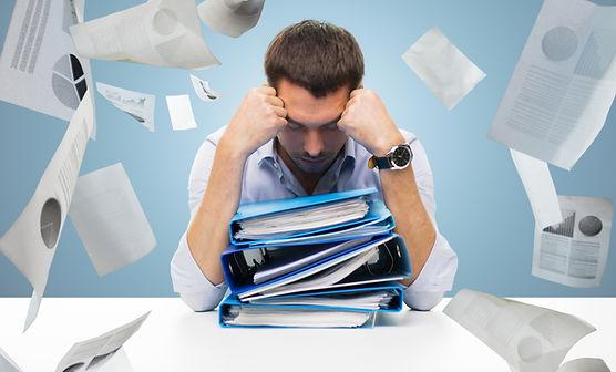 gestresseter Geschäftsman vor einem Stapel Ordner voller Dokumente