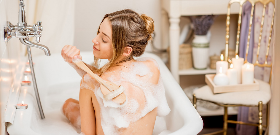 woman in bath scrubbing her back with brush