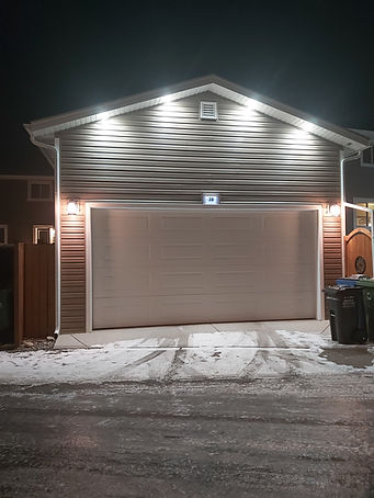 garage with pot lights, illuminated number sign and coach lights and soffit plugs