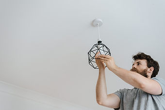 man hanging light in basement