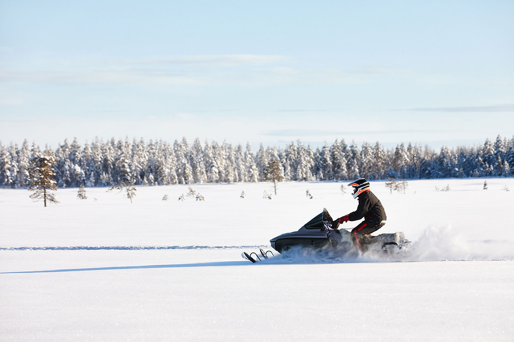 Man snowmobiling across a snow-covered field in Mammoth Lakes