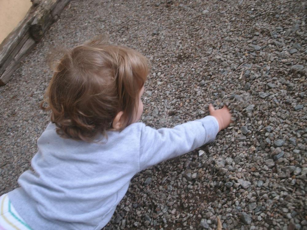 Criança engatinhando nas pedrinhas