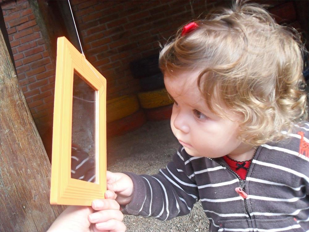 Criança se olhando no espelho