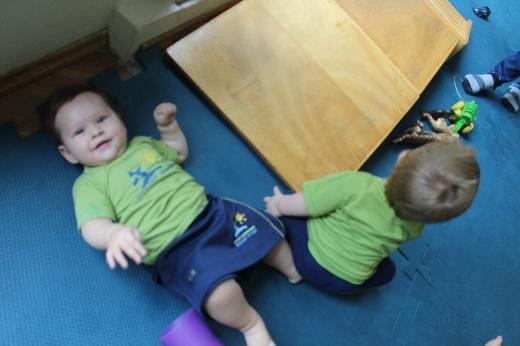 Bebês deitados no chão de borracha no berçário