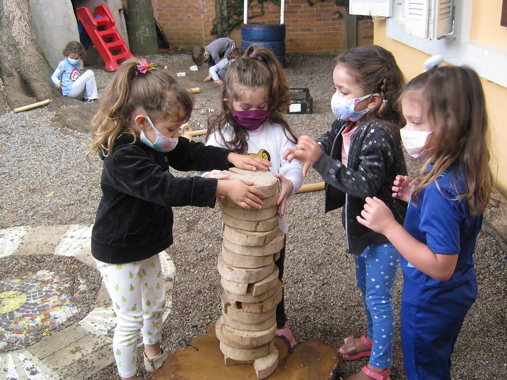 Quatro criança empilhando círculos de madeira