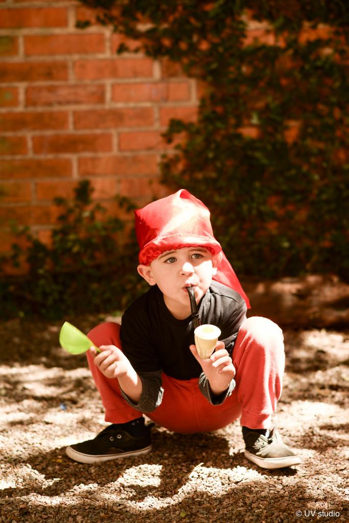 Criança vestida de Saci e com cachimbo na boca