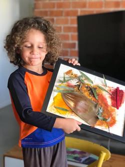 Menino mostrando quadro que fez