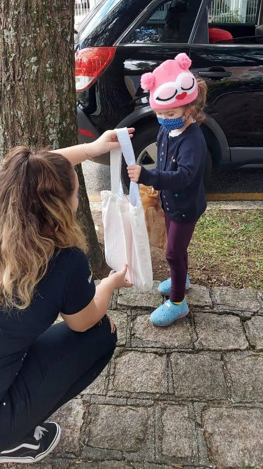 Professora Maria Eduarda entregando sacola para aluna