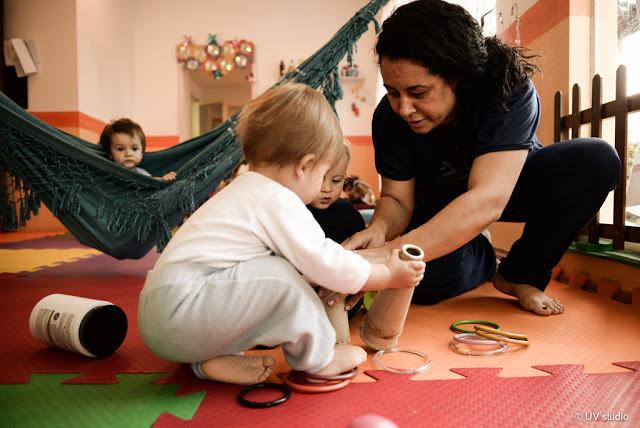 Berçarista brincando com os bebês