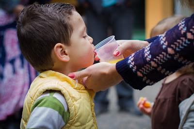 Mãe dando água para o filho